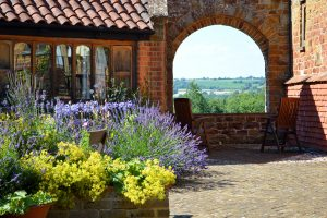 The archway in our courtyard looking out to the Cotswold hills, showing the stunning views from the holiday cottages